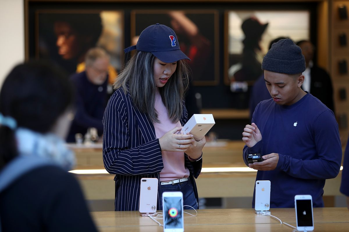Two customers shop for new iPhones in an Apple store.