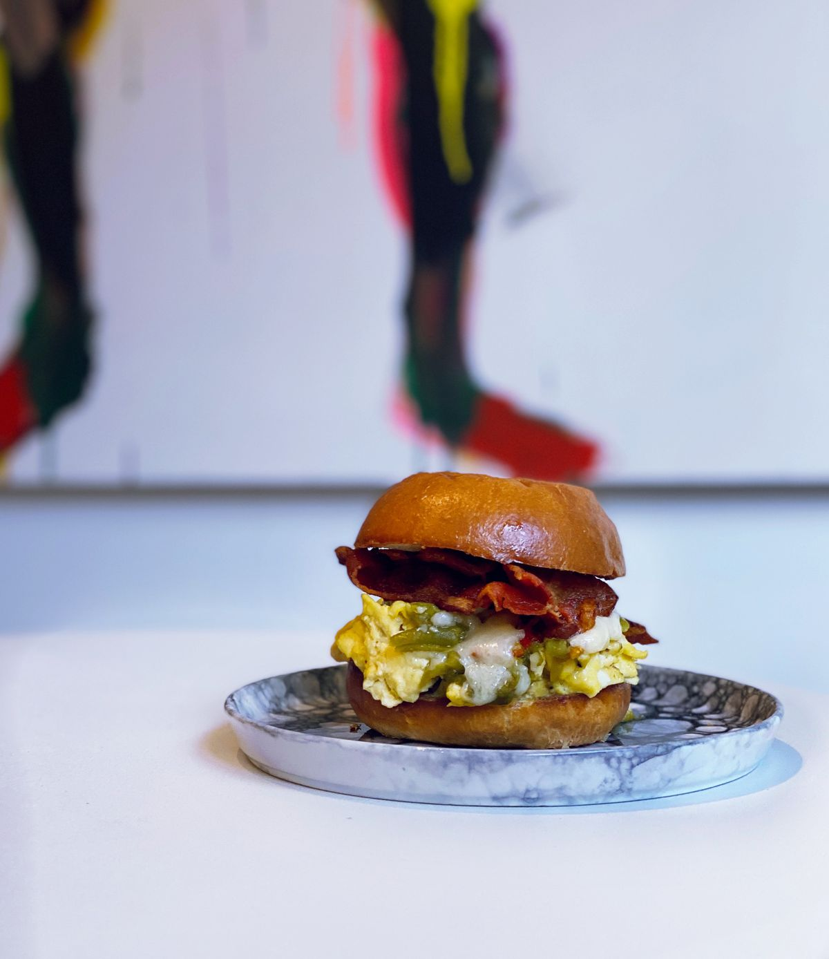Two buns sandwich a mass of eggs, and streaks of bacon on a marble plate.