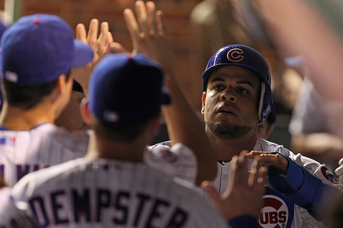 Aramis Ramirez of the Chicago Cubs is greeted by teammates in the dugout after scoring a run and hitting a run-scoring double in the 5th inning against the Atlanta Braves at Wrigley Field in Chicago, Illinois. (Photo by Jonathan Daniel/Getty Images)