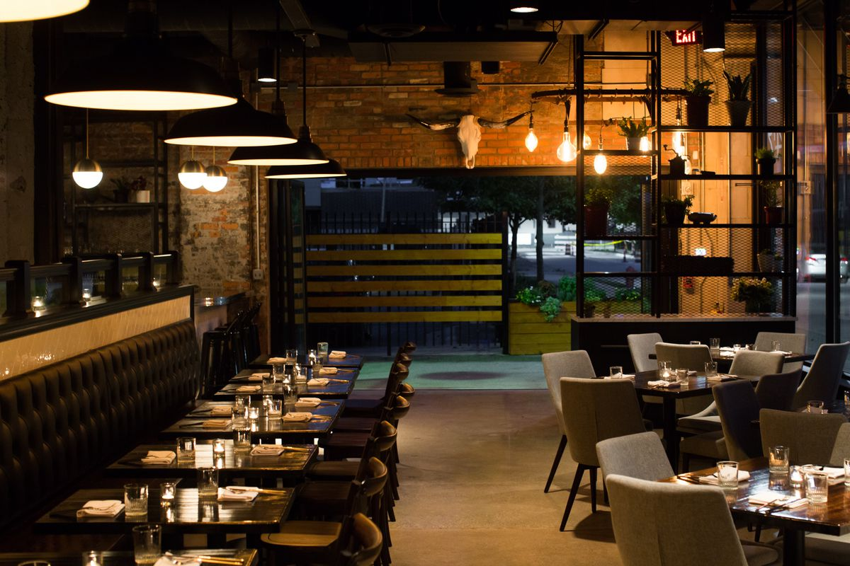 The dimly lit dining room at Grey Ghost features rows of tables along a banquette looking out into a patio. The chairs are black and the walls are brick with a bull skull hanging above the patio entrance.