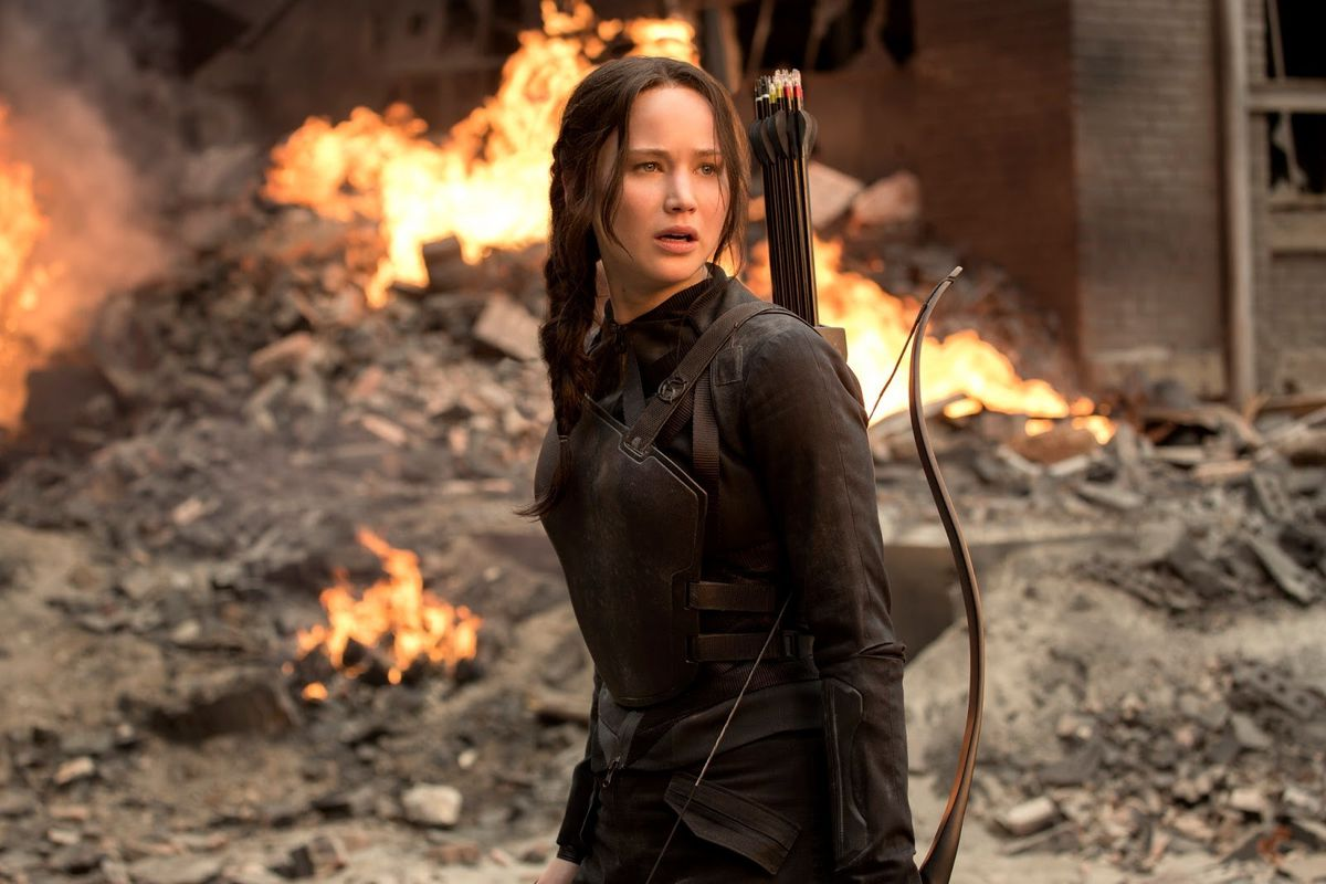 The Hunger Games - Katniss Everdeen standing in rubble with a bow slung over her shoulder and fire behind her