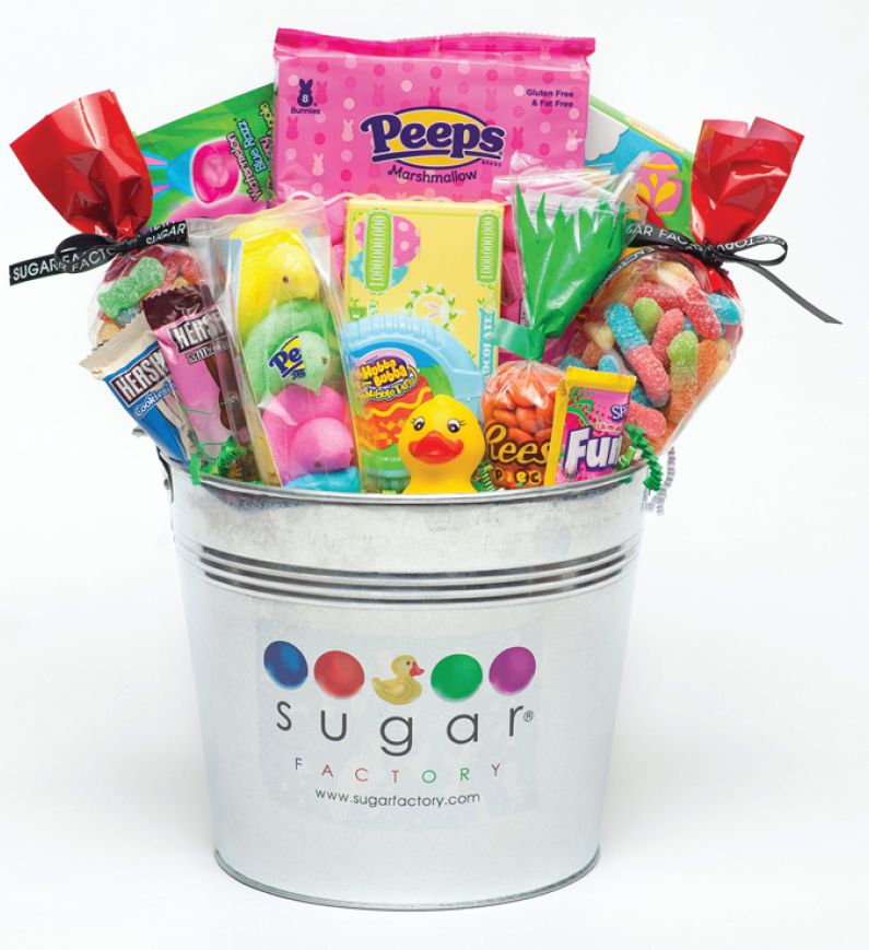 An Easter bucket filled with marshmallow Peeps, a Hershey's cookies n' cream bunny, a Hershey's chocolate bunny, Starbursts, Hubba Bubba bubble tape, springtime fun dip, a Reese's Pieces candy bag, and two Sugar Factory candy bags filled with Sour Patch Kids and gummy sour worms