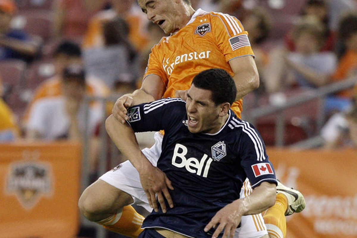 HOUSTON - APRIL 10:  Cam Weaver #15 of the Houston Dynamo goes over the top of Michael Boxall #2 of the Vancouver Whitecaps for a header in the second half at Robertson Stadium on April 10, 2011 in Houston, Texas.  (Photo by Bob Levey/Getty Images)