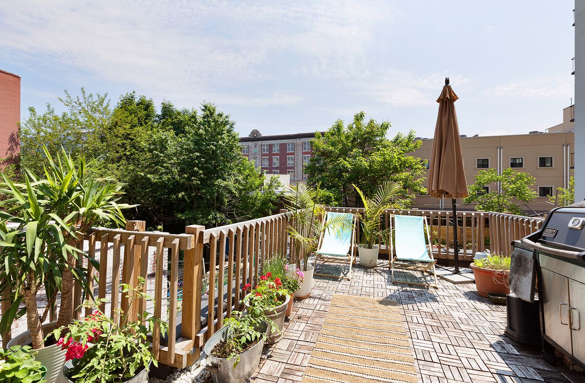 A terrace with wooden fencing, a grill, several planters, and two chairs.