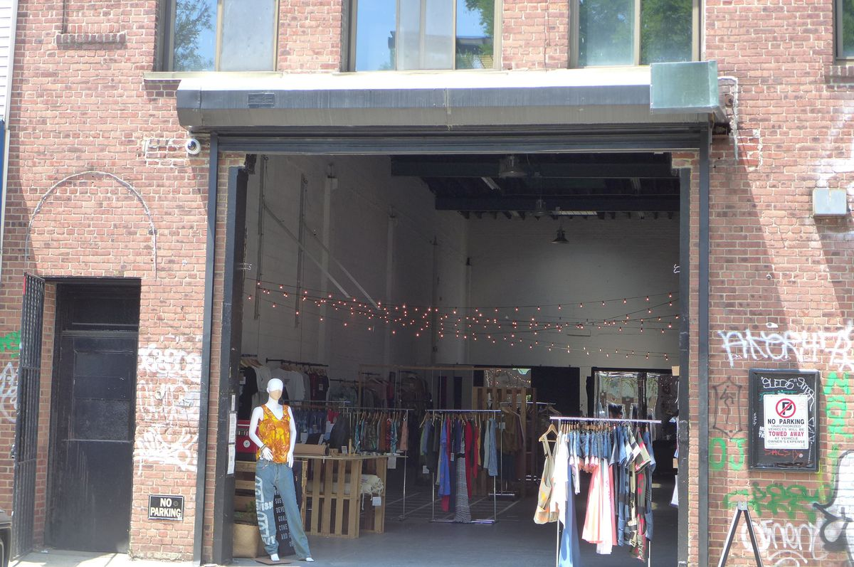 A big open storefront with a mannequin on one side and rack of used clothes on the other.