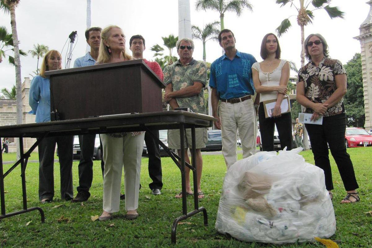 Nancie Caraway, Hawaii's first lady, speaks at a podium next to a pile of plastic bags during a news conference in Honolulu, Thursday April 19, 2012. Caraway joined environmental groups in calling on state lawmakers to vote on a bill that would charge a 1