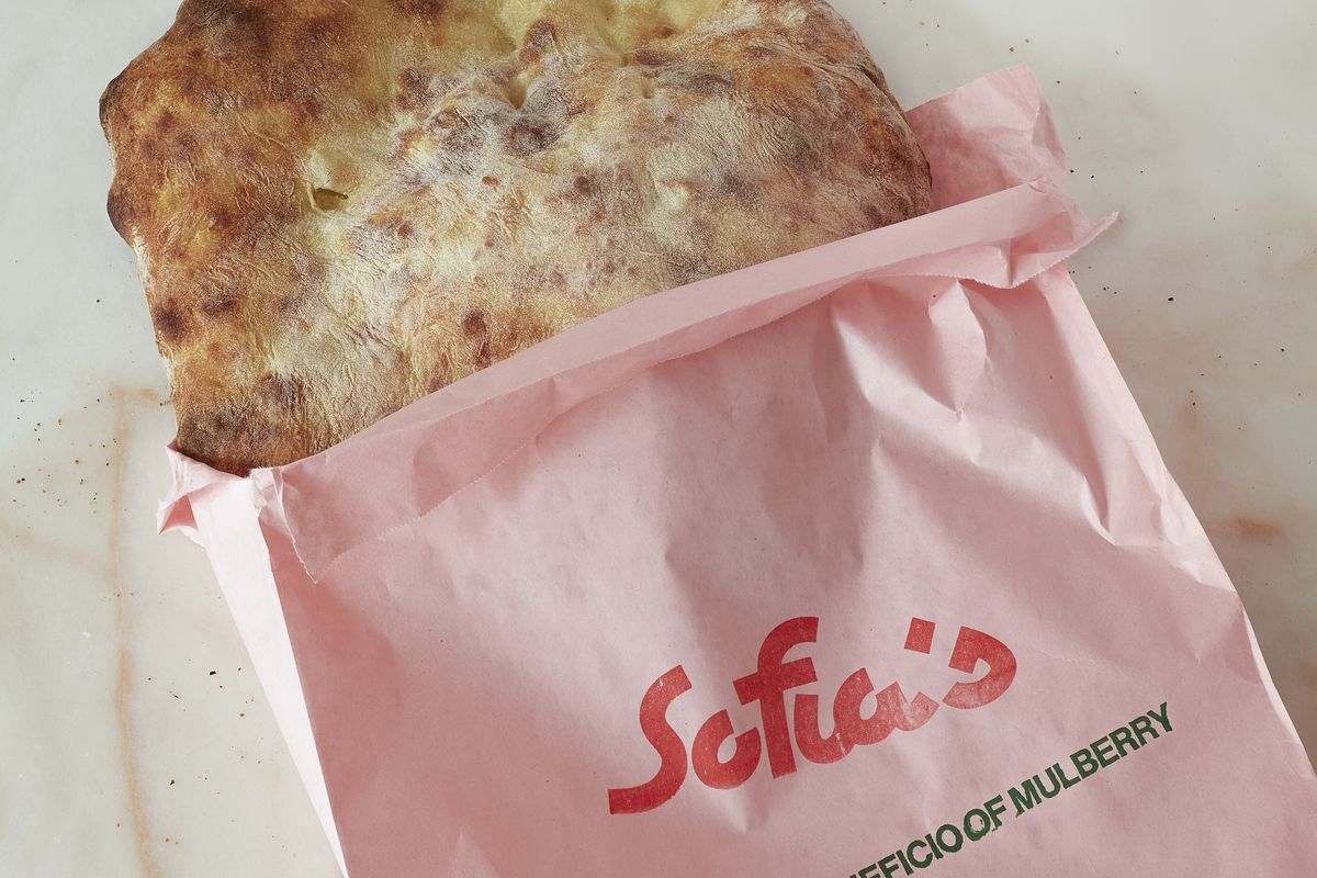 """Pizza bianca flatbread pokes out of a pink takeout bag with the word """"Sofia's"""" in red lettering"""