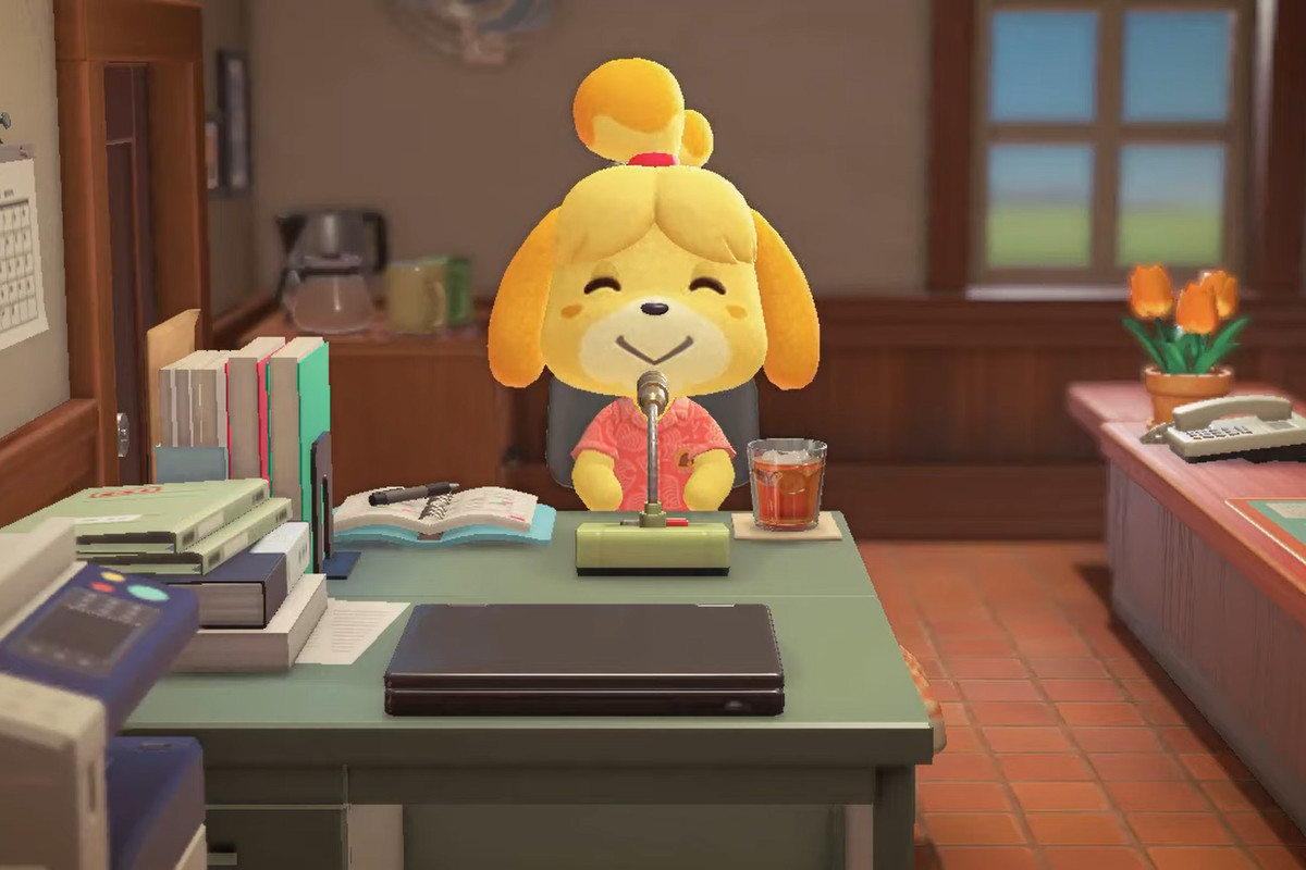 Isabelle with a red floral shirt sitting at her desk doing announcements