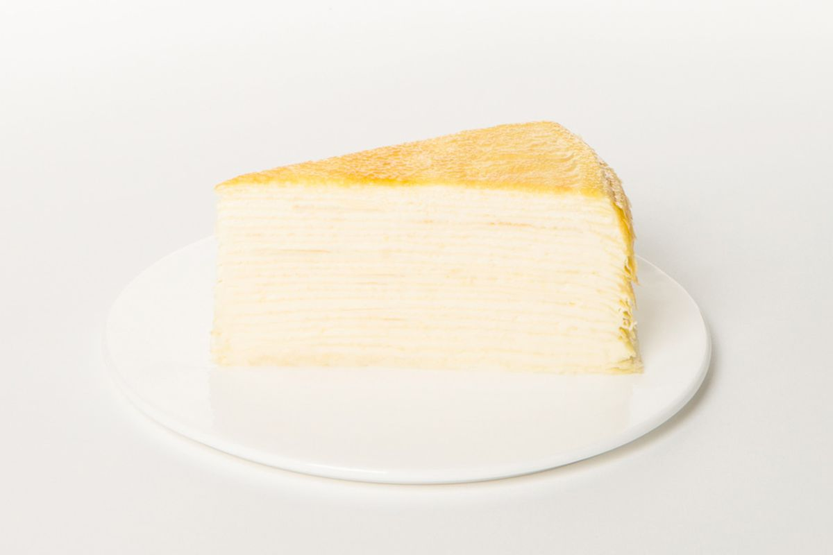 A layered crepe cake on a white plate