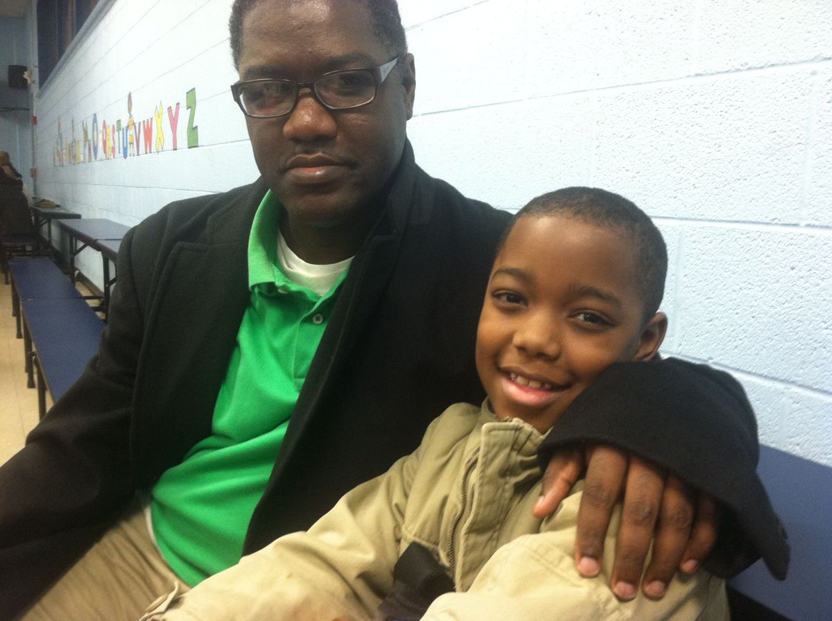 Mark West and his third-grade son at a hearing regarding the proposed closing of Alcy Elementary School.