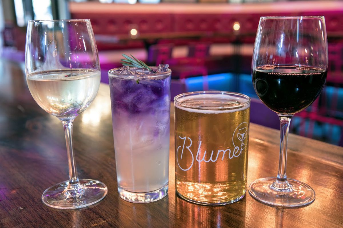 row of drinks with wine, cider, and a purple cocktail