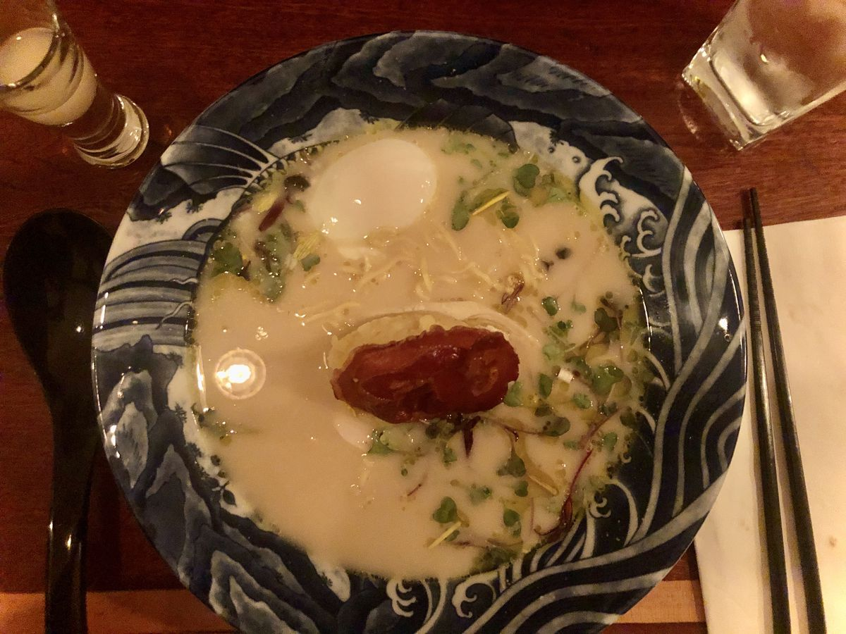 Ramen with mashed potatoes, bacon, egg, and microgreens in a blue and white bowl with black chopsticks and a soup spoon placed on either side of the bowl