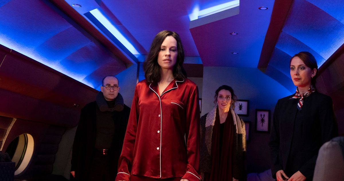 Hilary Swank, in red pajamas, looks disdainfully toward something below the level of the screen, in a blue-lit space with framed scorpions and beetles on the wall, as three fully dressed people circle her.