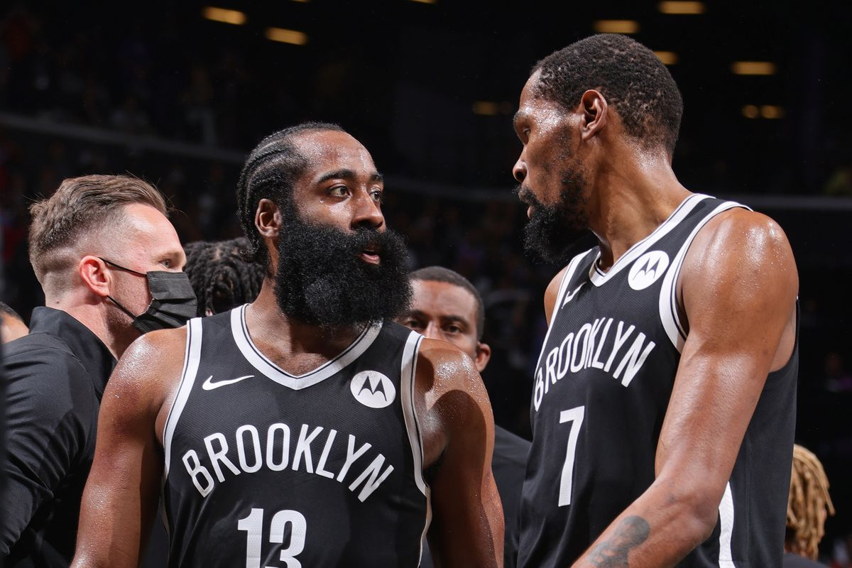 James Harden #13 talks with Kevin Durant #7 of the Brooklyn Nets during Round 2, Game 7 of the 2021 NBA Playoffs on June 19, 2021 at Barclays Center in Brooklyn, New York.