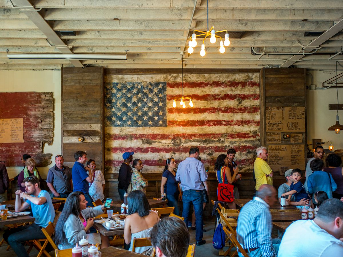 The dining room at HometownBar-B-Que, with an American flag mural on the wall