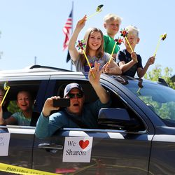 A family waves and cheers as they drive past residents at The Ridge Cottonwood assisted living center in Holladay during a Mother's Day parade on Saturday, May 9, 2020.