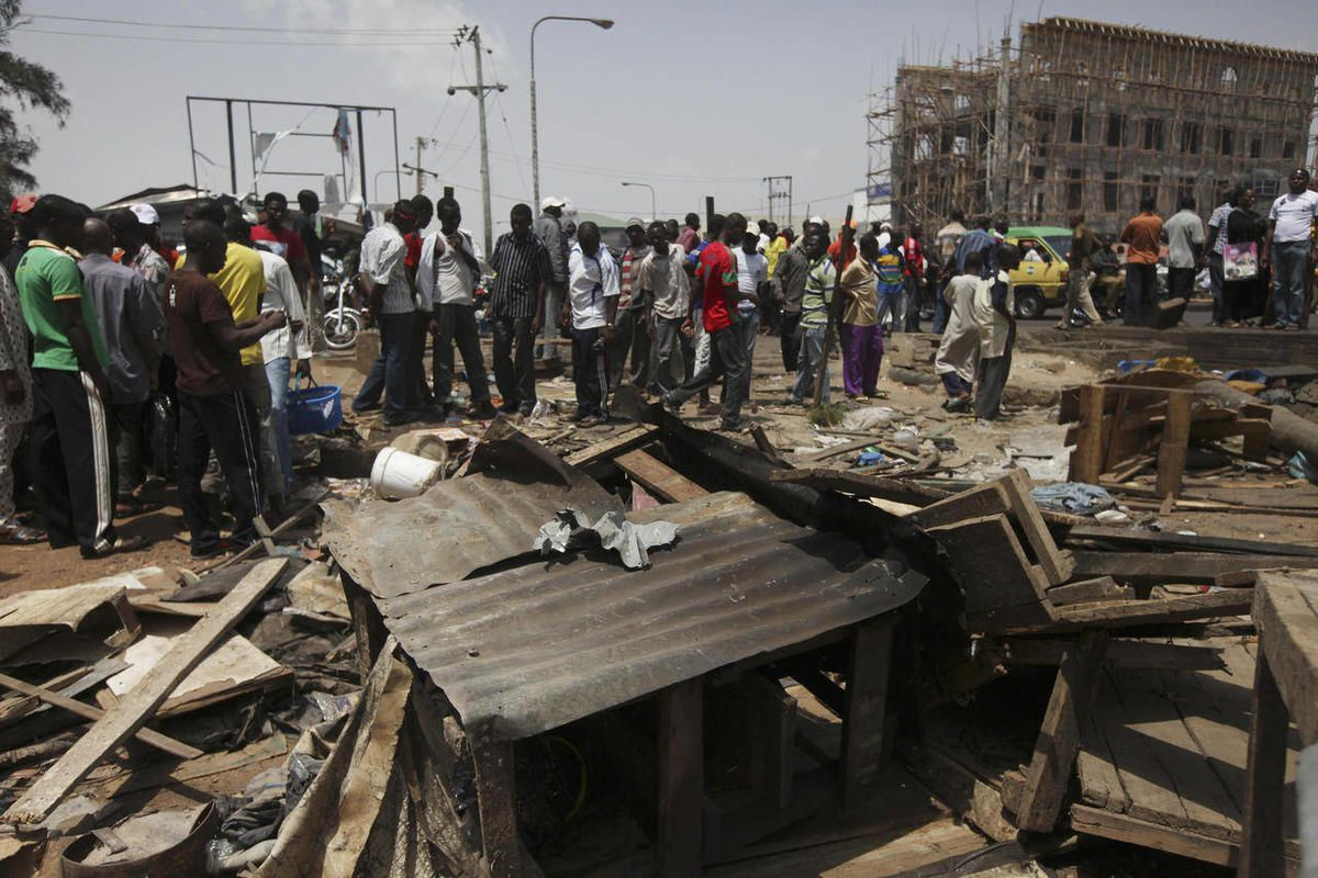 People gathered around the  wreckage of a damaged road side tea shop following an explosion in Kaduna, Nigeria  Monday, April 9, 2012. A suicide car bomb that killed at least 38 people in Nigeria over the weekend affected Nigerians across religious and et