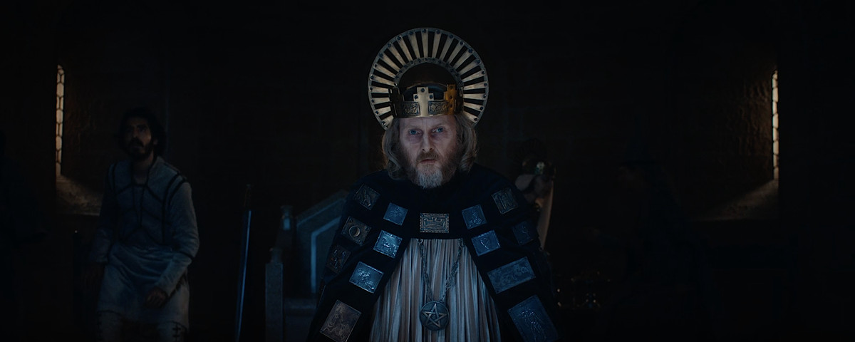 Sean Harris as King Arthur, standing in his court, lit from above, in The Green Knight