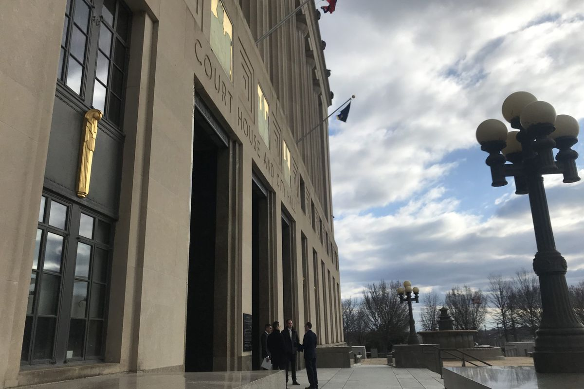 Attorneys huddle outside of the Davidson County Courthouse on Friday before the first hearing over the first legal challenge to Gov. Bill Lee's education savings account program.