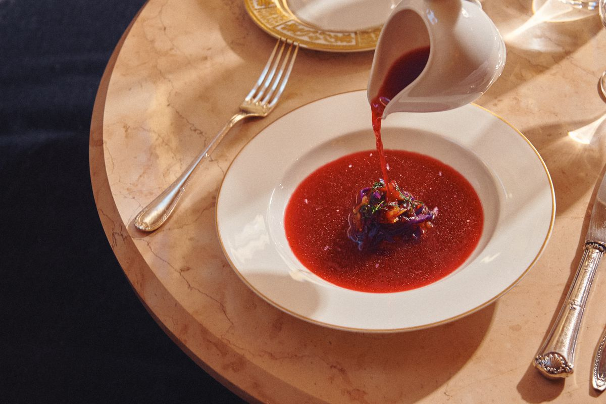 A white ceramic pot of red soup pours into a shallow white bowl.