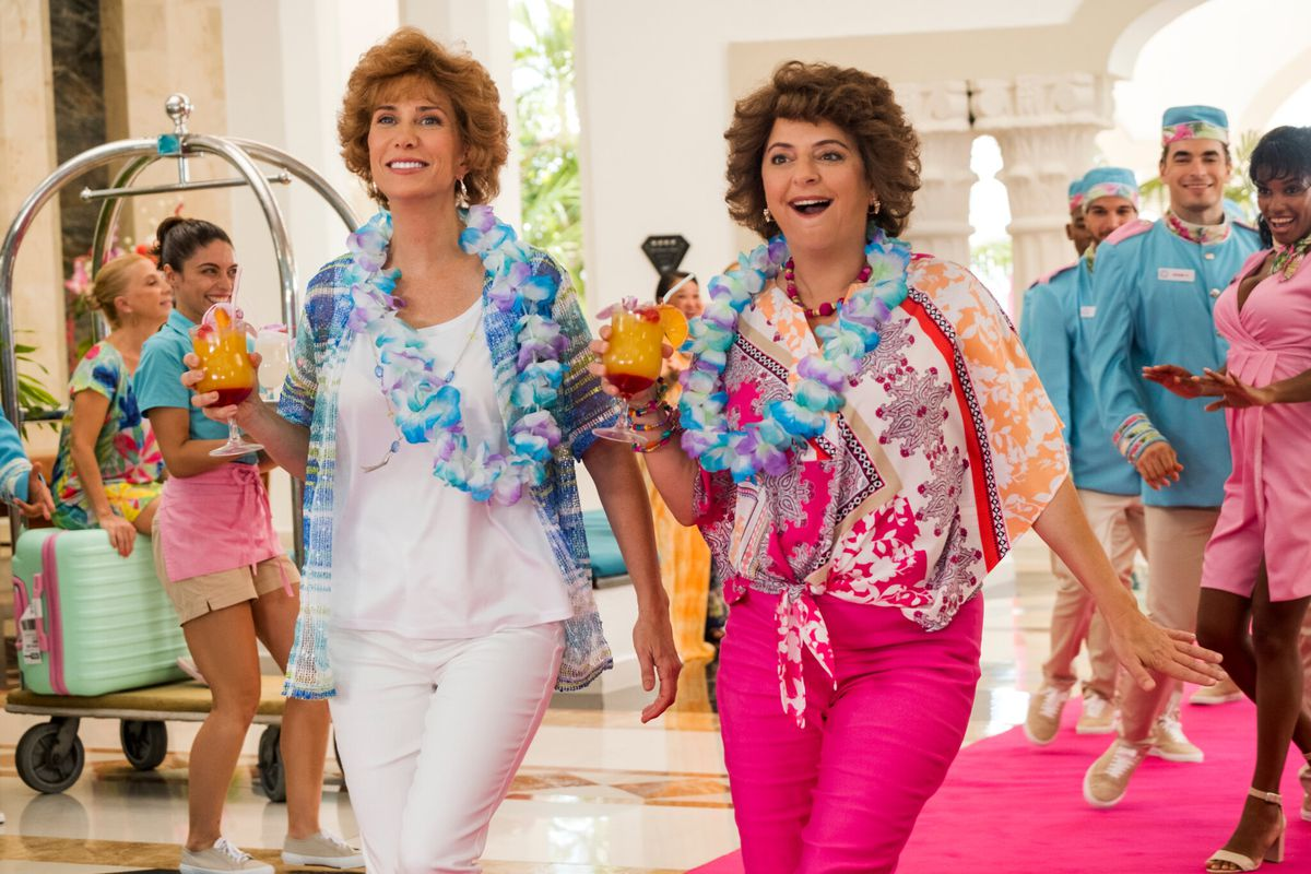 Two women with cocktails in their hands smile as they enter a resort hotel.