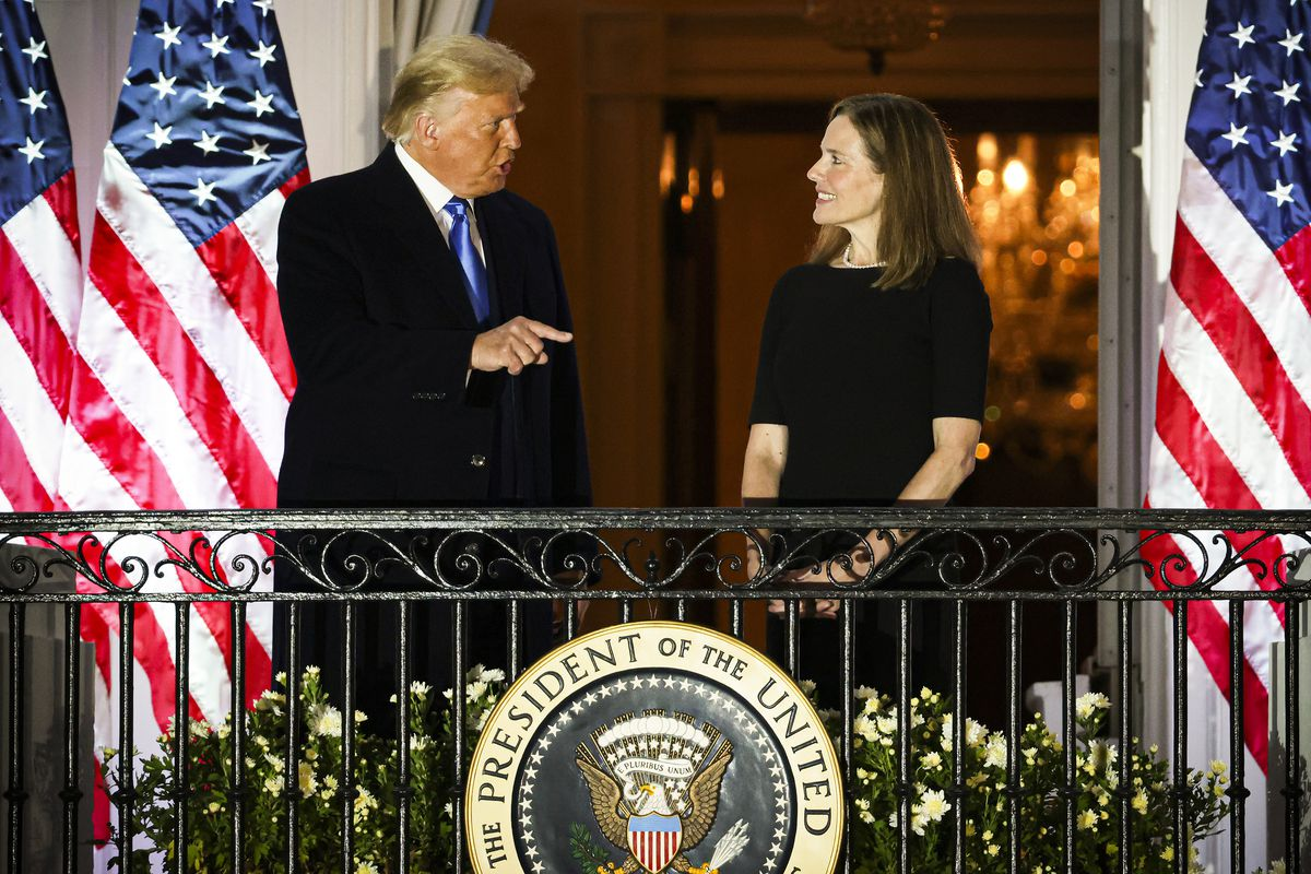 Donald Trump and Amy Coney Barrett talk on a balcony overlooking the South Lawn of the White House