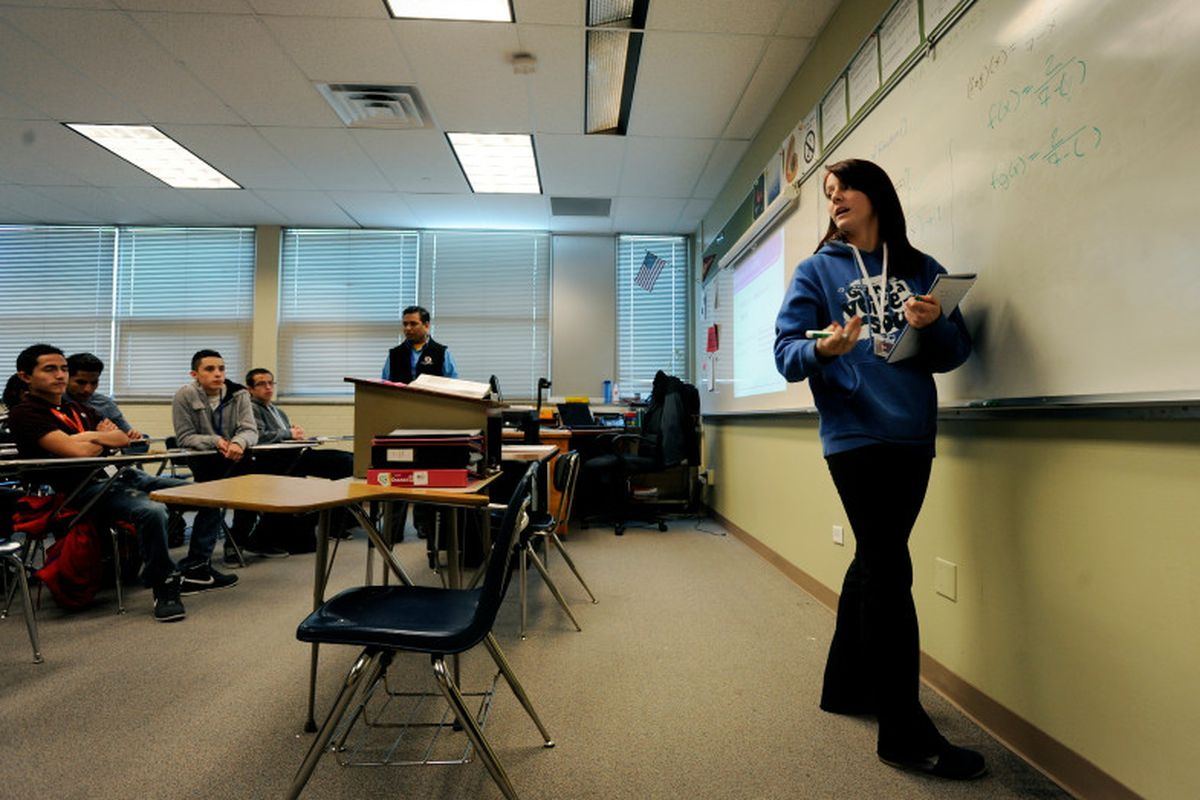 Hinkley High School student Catherine Gibson turns toward her college algebra class to explain a problem she works on the board in 2013 at Hinkley High School in Aurora, Colo. (Photo by Jamie Cotten, Special to The Denver Post)