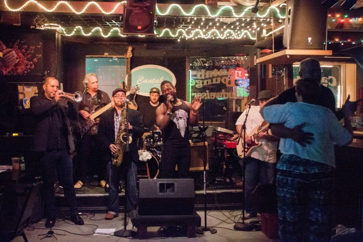 A band with saxophone, trumpet, bass, guitar, and more plays in a small, casual bar. A couple dances in front of them.