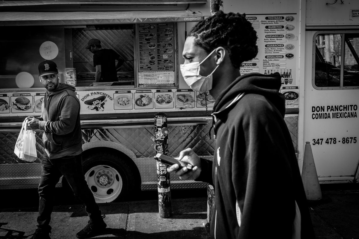 A man in a mask walks by a food truck