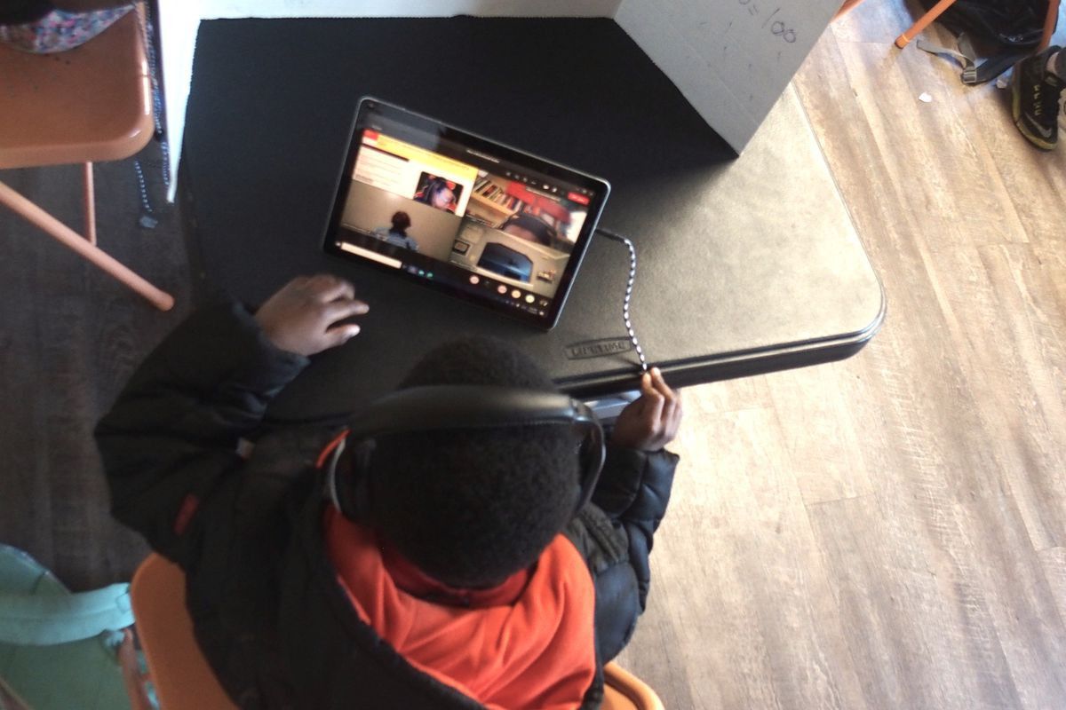 A young boy in a black and orange hoodie conducts virtual learning on his computer, sitting at a black partitioned desk.