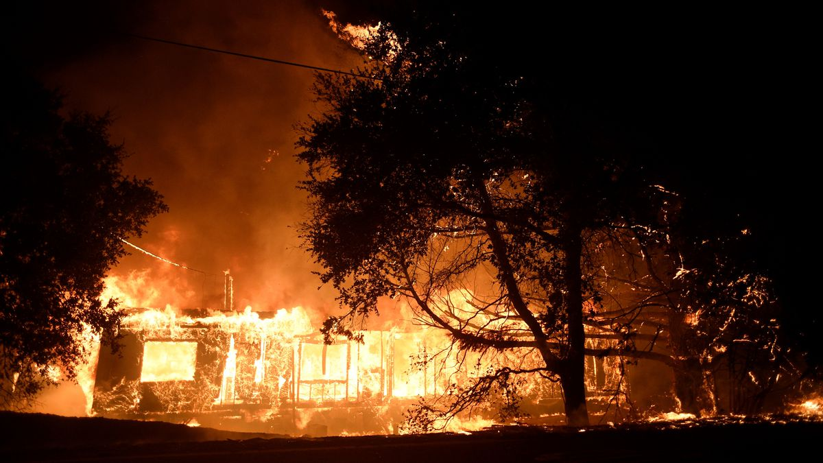 Flames consume a house with trees silhouetted in the foreground.