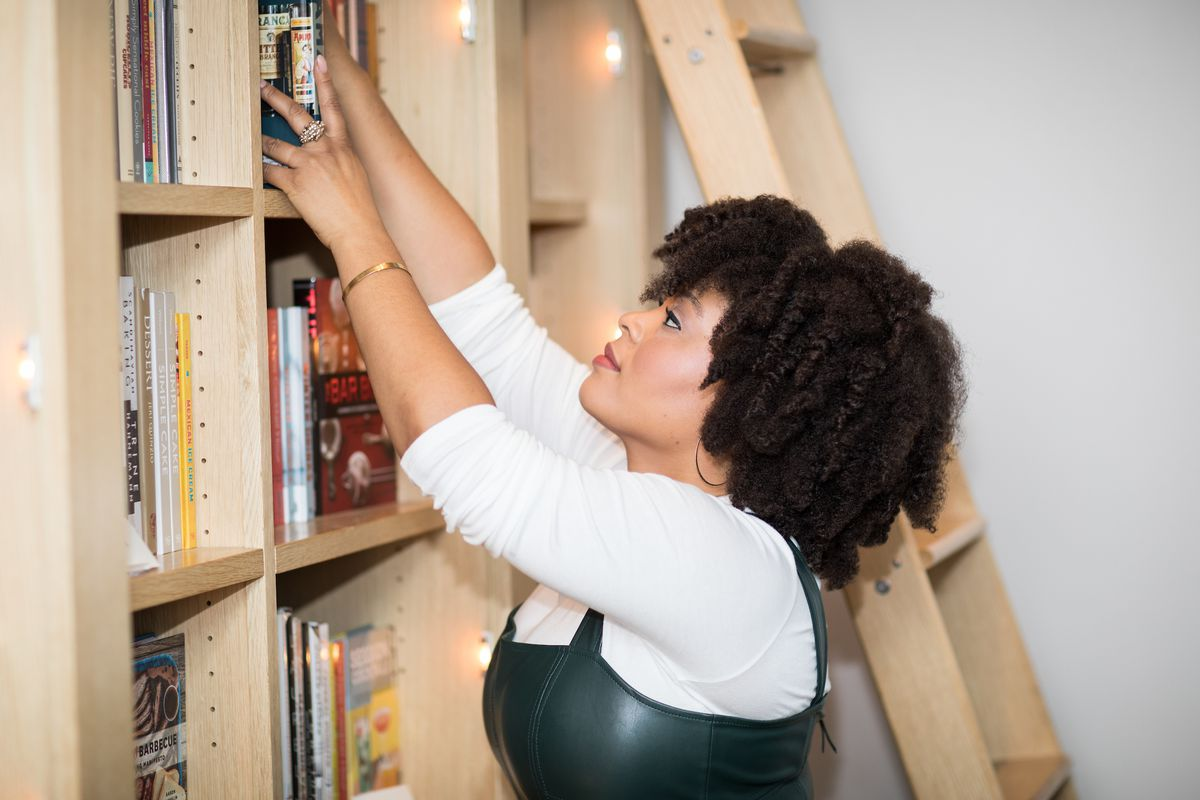 Woman reaches for a book in a library.