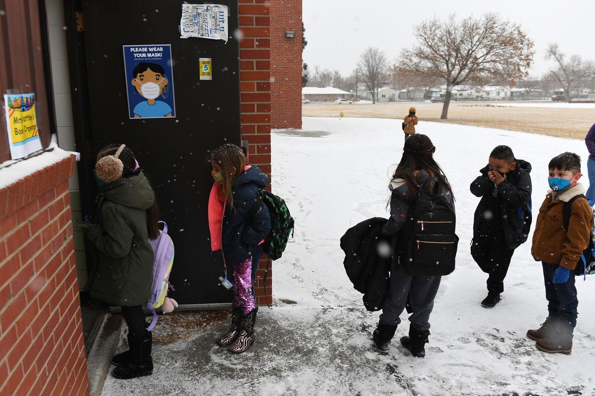 Young children in masks and winter coats line up to enter an Adams 14 school building on a snowy day.