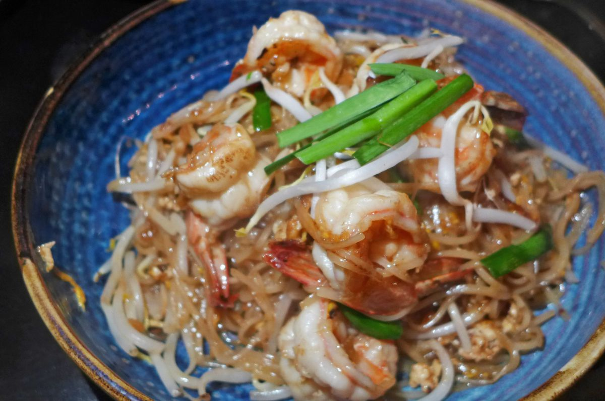 A mass of reddish noodles with shrimp and sprouts.