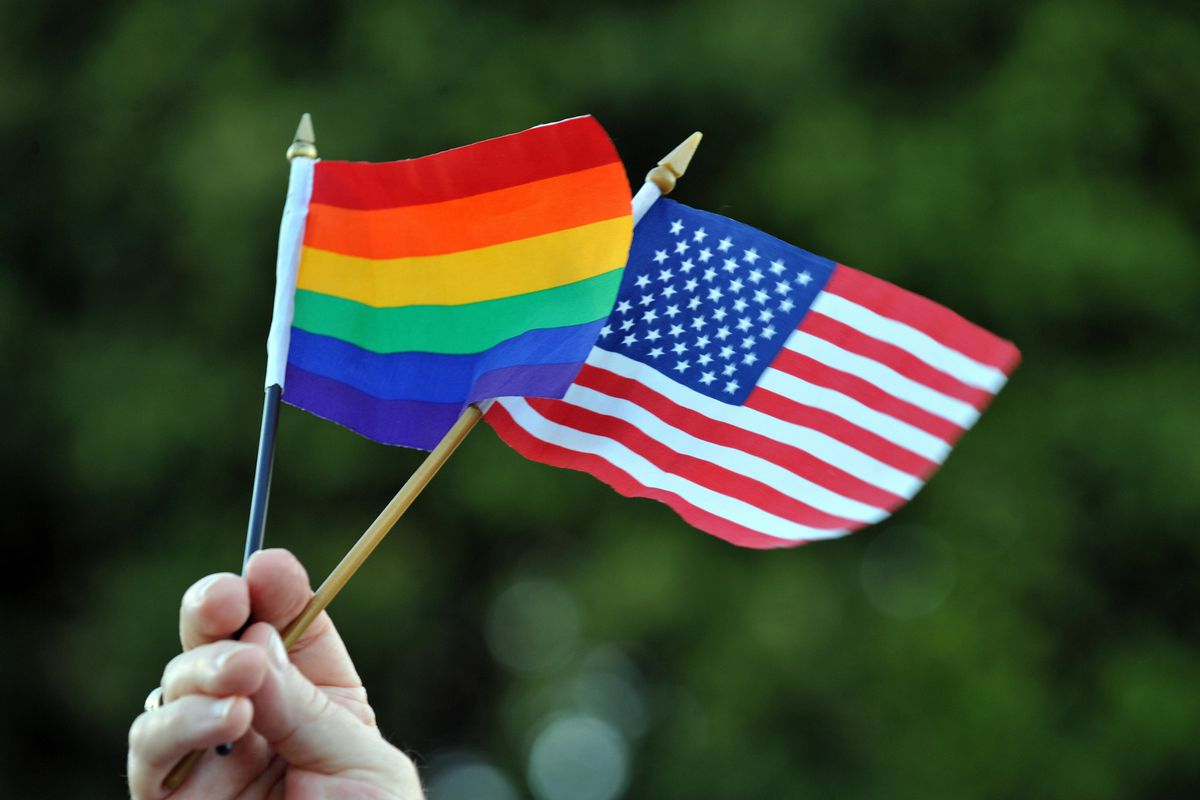 A man holds up an LGBT Pride flag with a US flag at a demonstration in California.