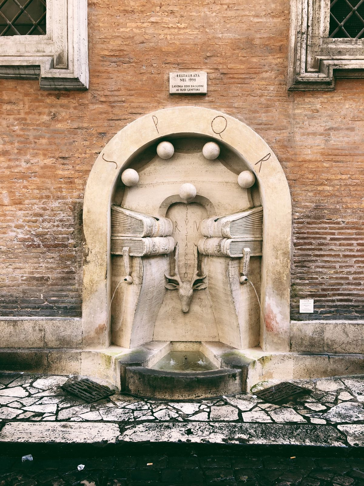 A fountain with an arched detailing against a brick wall.