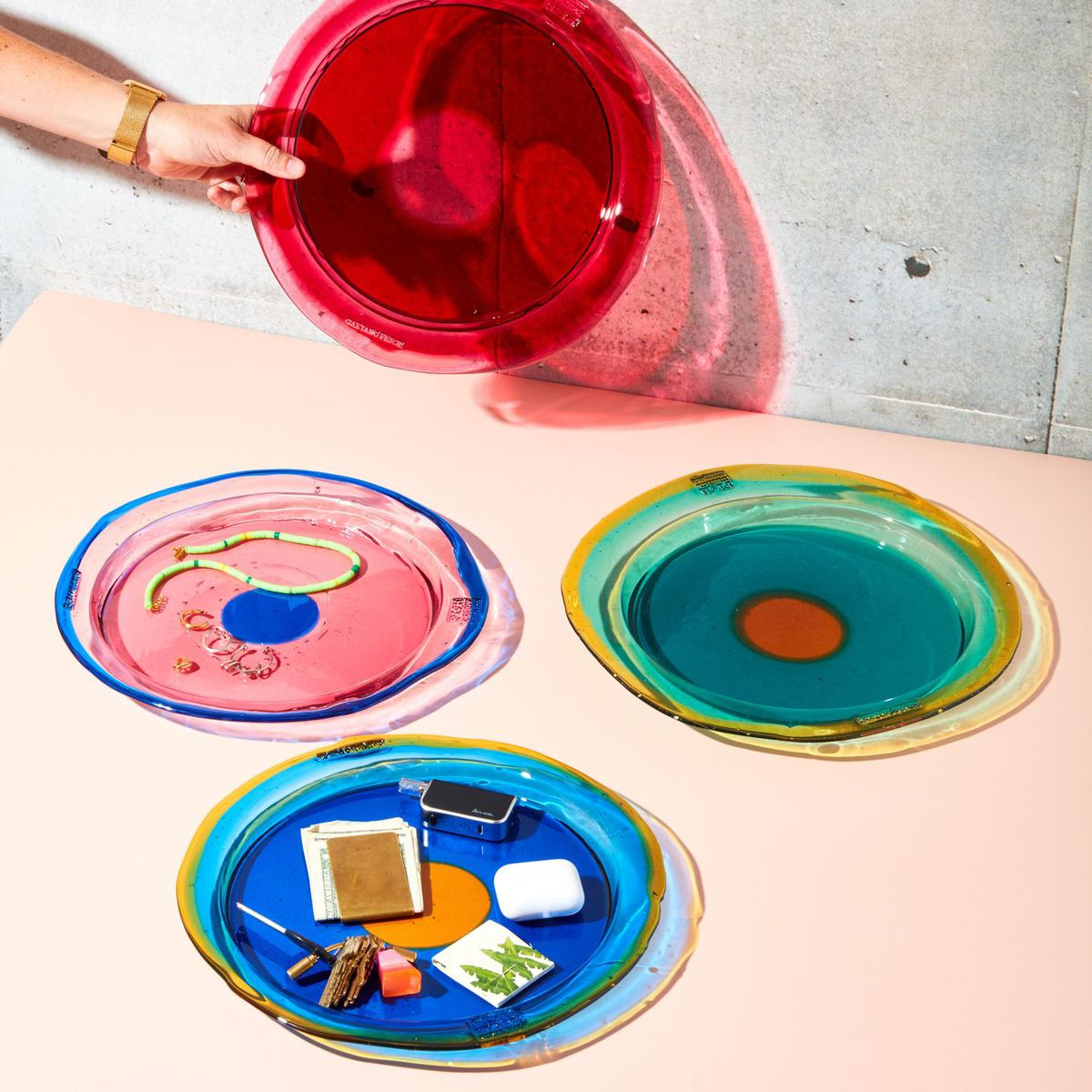 Four bright glass plates in the colors red, pink, green, and blue are positioned on top of a pink table.