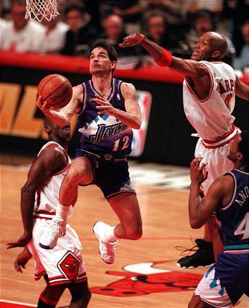 Jazz point guard John Stockton drives past Michael Jordan.