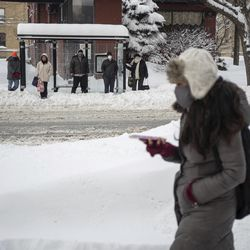Commuters wait for a bus in the Edgewater neighborhood Tuesday after a snowstorm hit Chicago.
