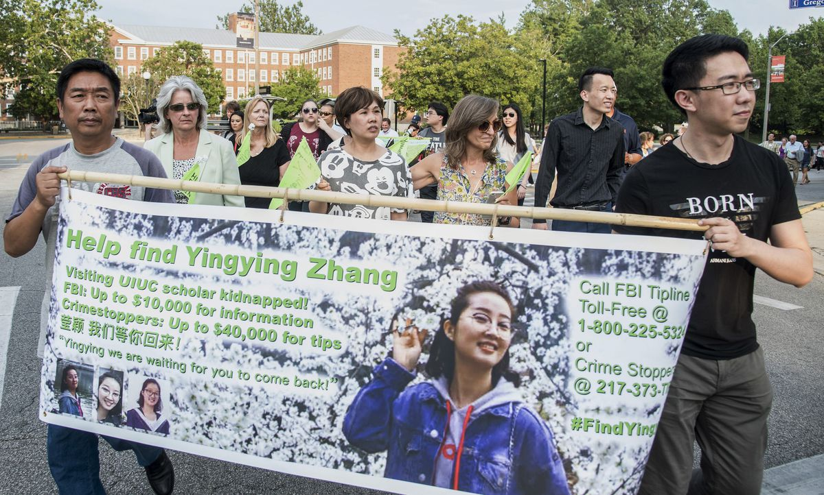 Yingying Zhang's father Ronggao Zhang (left) and her friend Xiaolin Hou carry a banner as community members walk for Yingying, a Chinese scholar who went missing in early June.