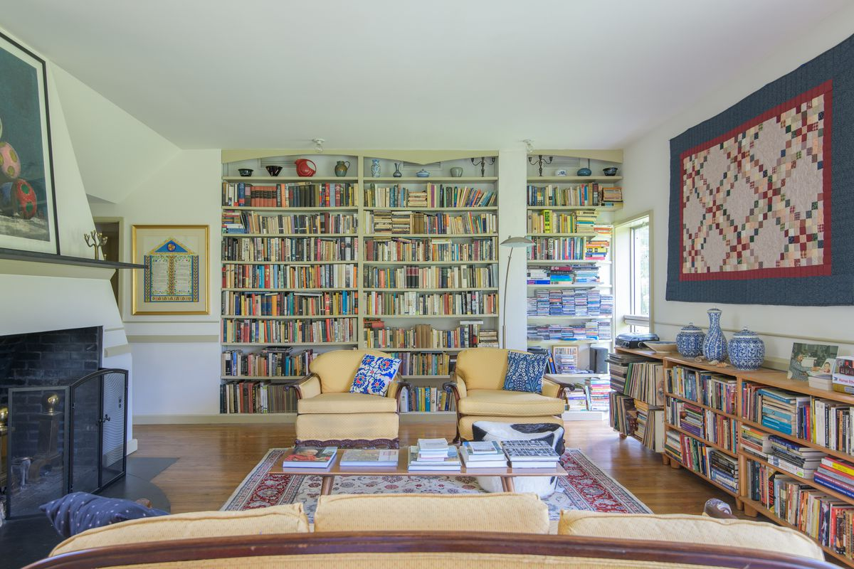 The living room of the Vanna Venturi house. There are multiple bookcases full of books, a fire place, a couch, two armchairs, and a patterned area rug. A patterned quilt and other works of art hang on the walls.