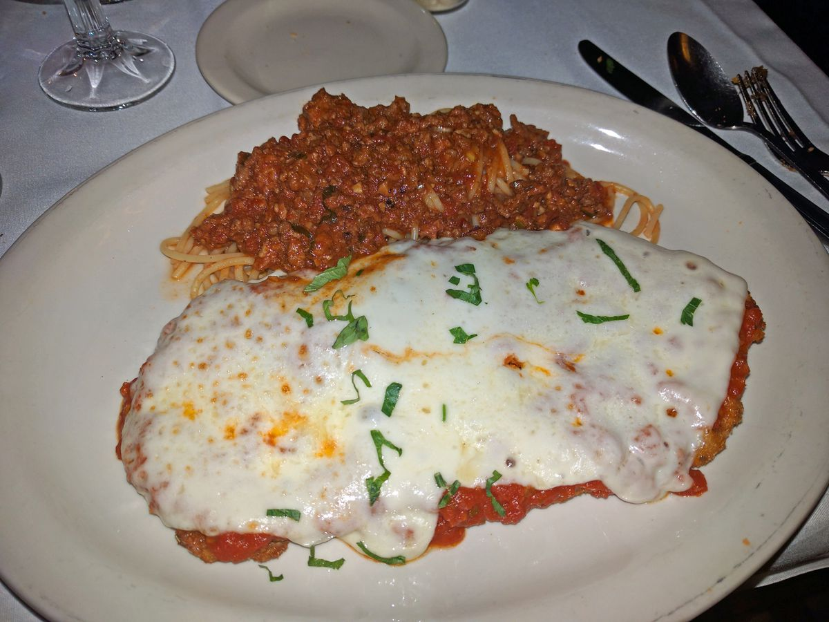 A veal cutlet smothered in cheese with spaghetti and meat sauce above it.