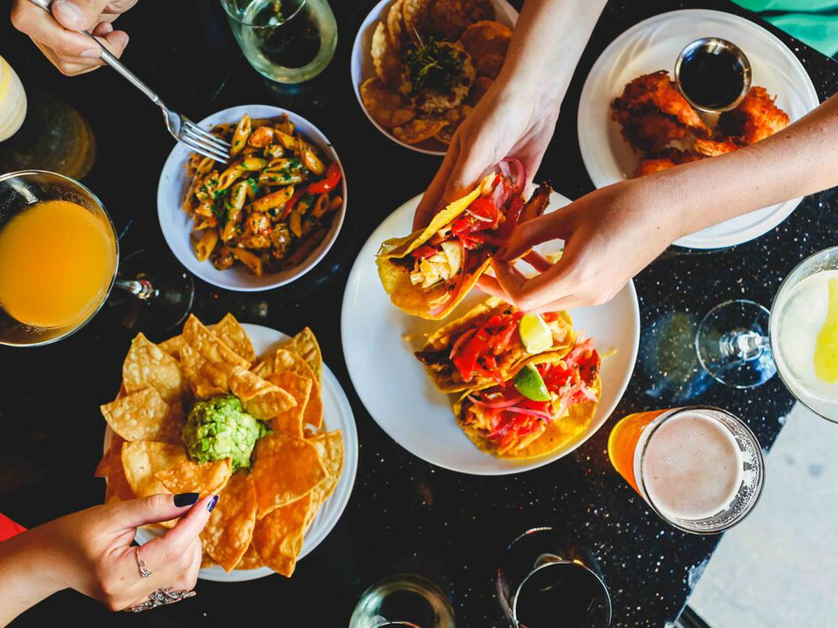 Hands reach in for plates of tacos, tortilla chips and guac, and penne pasta.