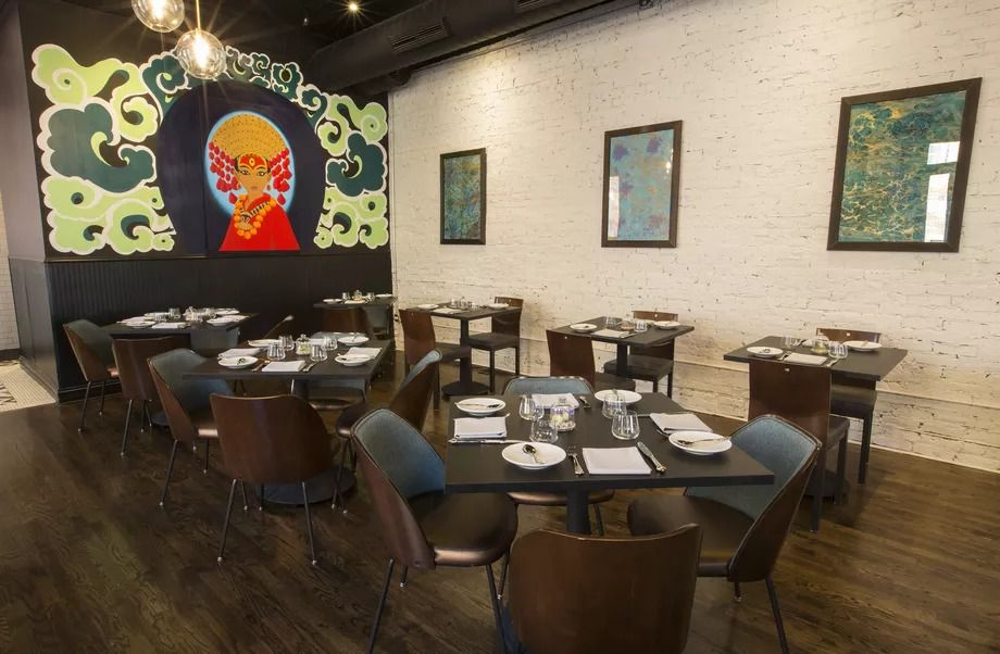 Vajra's dining room features brown tables and chairs, white brick walls, framed artwork, and an Indian mural