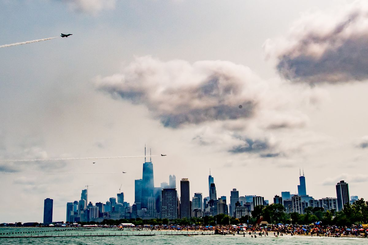 Planes with smoke trails fly in different directions above the Chicago lakefront. The beaches are packed with onlookers and the Chicago skyline is visible beyond.