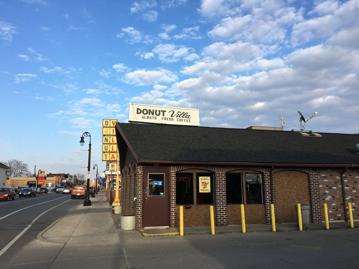 The brown brick exterior of Donut Villa is shown on a sunny day.