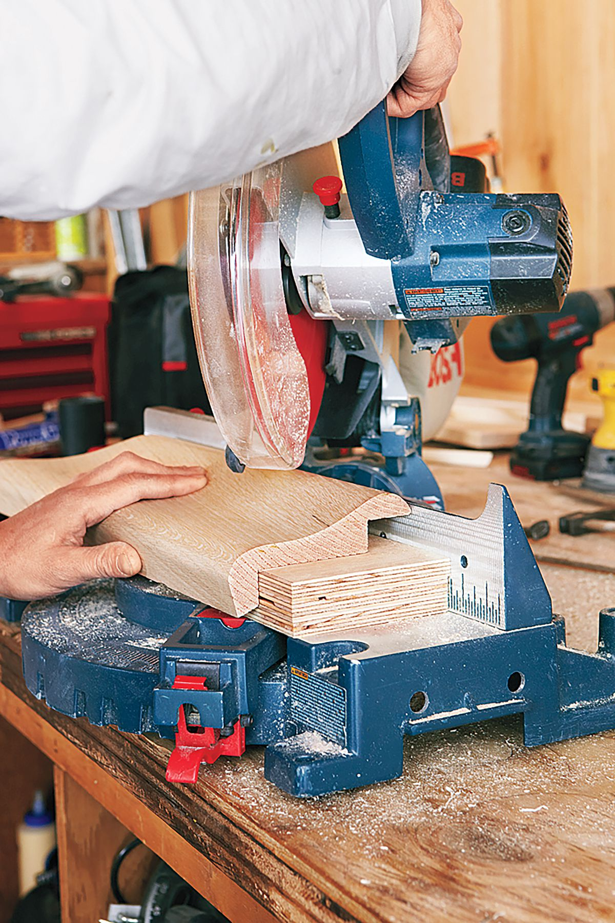 Person Using Miter Saw To Cut Bar Molding