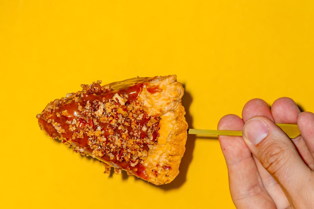 A hand holding a caramel-dipped pecan pie on a stick against a yellow background