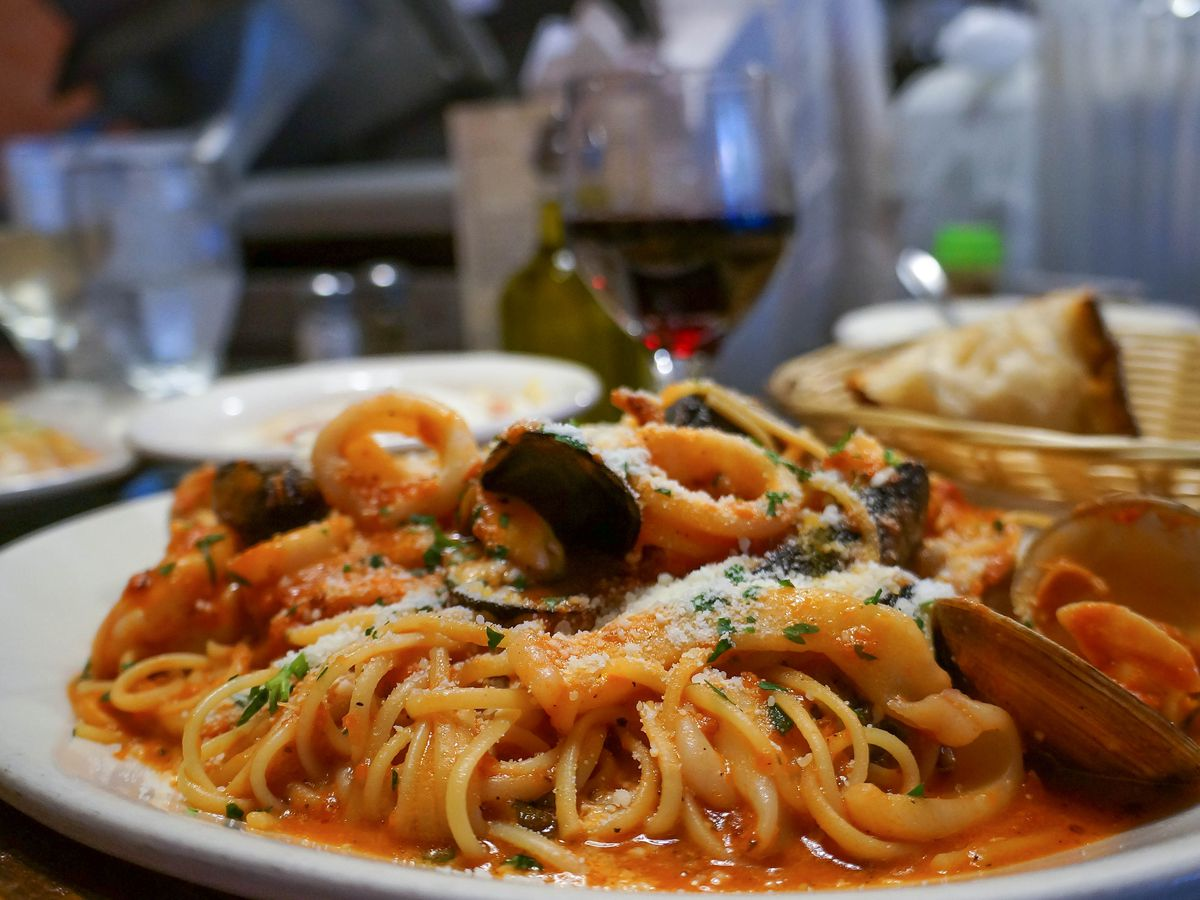 Spaghetti in a tomato sauce, piled on a white plate and topped with clams and other seafood. A basket of bread and glass of wine are visible in the background.
