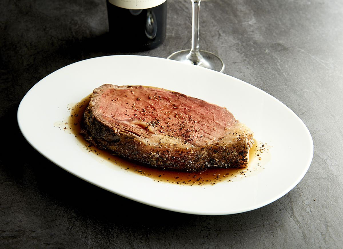 A slab of pink prime rib sits on a white plate, topped with pepper and swimming in its own juices.